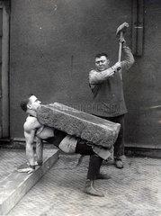 Mann zerschl_gt Steinblock auf Bauch eines Mannes