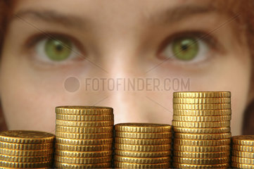 gruene Augen einer Frau hinter 50-Cent-Muenzen-Stapel