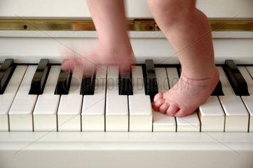 Baby mit Fuessen auf Klaviertasten