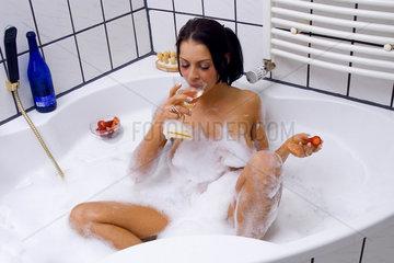 Frau in der Badewanne isst Erdbeeren und trinkt Sekt