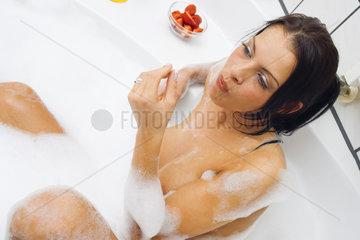 Frau in der Badewanne isst Erdbeeren