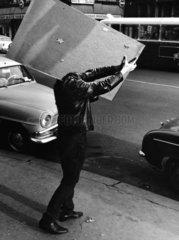 kopflos wirkender Mann transportiert Spiegel