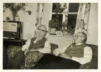 zwei Maenner unterhalen sich und hoeren Radio  1957