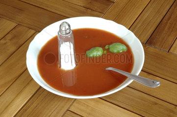 Salzstreuer steht in einem Teller Tomatensuppe