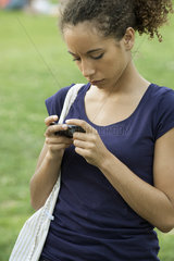 Young woman text messaging with cell phone