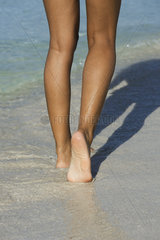 Woman walking in surf at the beach  low section