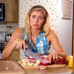 Frau weint beim Schneiden von Zweibeln