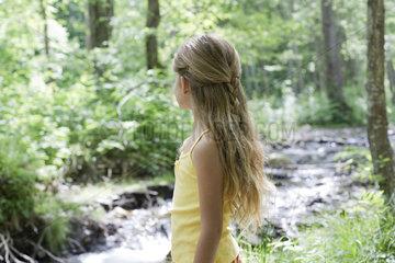 Girl by stream in woods  looking away