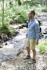 Man hiking along stream in woods