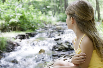 Girl contemplating stream in woods
