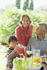 Boy and grandparents having meal outdoors