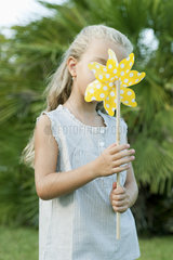 Girl holding pinwheel in front of face  portrait