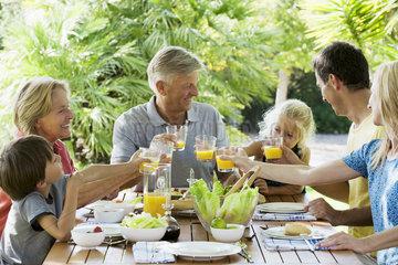 Multi-generation family toasting with orange juice outdoors  portrait