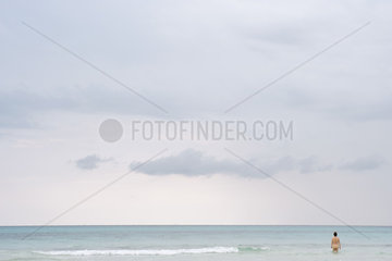 Solidary nude figure wading in sea