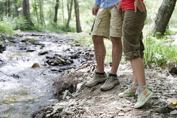 Couple hiking along stream in woods  low section