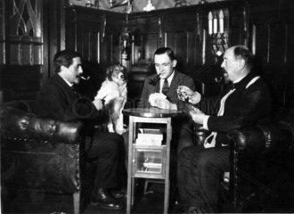 drei Maenner im Salon beim Karten spielen