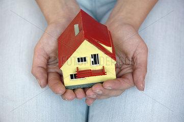 zwei Haende halten Miniatureigenheim