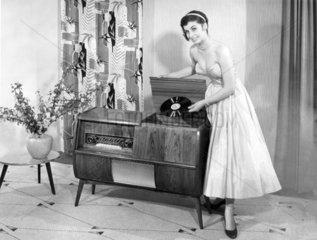 Frau posiert mit Plattenspieler und Platte