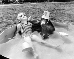 Maedchen mit Affe im Swimmingpool