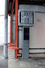 Muenzautomat an einer renovierungsbeduerftigen Waschstrasse fuer Autos.