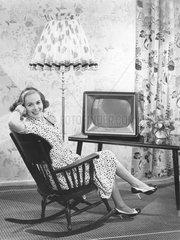 Frau sitzt vor Fernseher in Schaukelstuhl