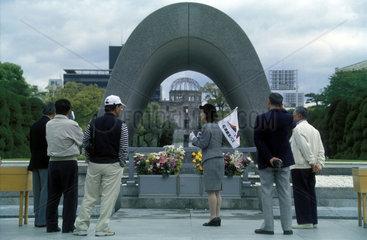 Menschen stehen an einem Denkmal