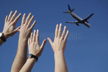 Haende winken Flugzeug zum Abschied