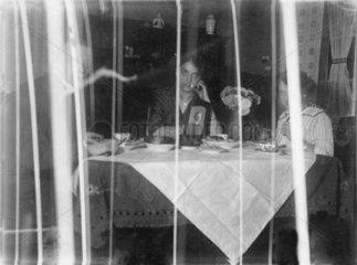 Familie sitzt am Essenstisch hinter Gardine