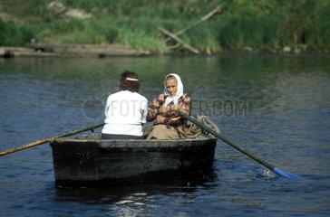 aeltere Dame rudert ein Ruderboot