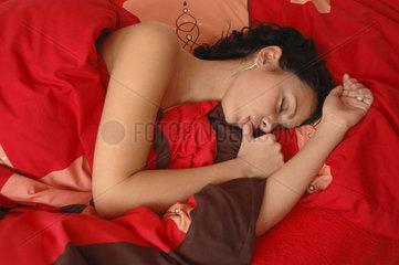 Frau liegt im Bett und nuckelt am Daumen