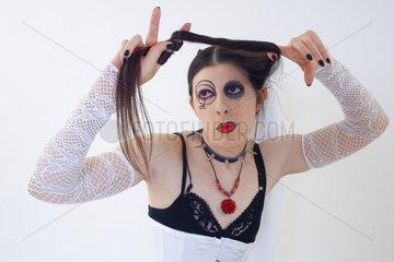 Frau als Gruftie geschminkt spielt mit ihren Haaren