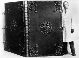 Mann steht neben Riesenatlas 1930