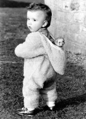 Kind traegt Frettchen in der Kapuze