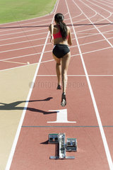 Woman running on track  rear view