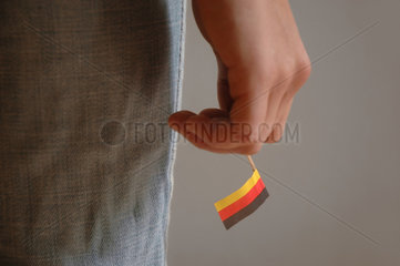 Hand haelt winzige Deutschandfahne
