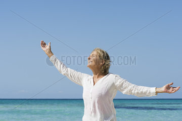 Senior woman by sea with arms outstretched  portrait