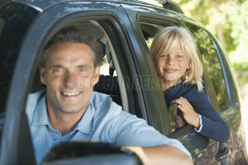 Boy riding in car with father  leaning out window and smiling at camera