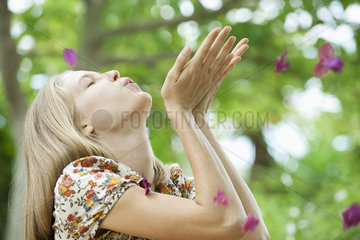 Young woman blowing purple flowers