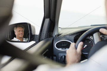 Man driving car  reflected in driver's side mirror
