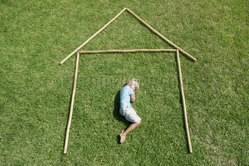 Boy lying on grass within outline of house  high angle view