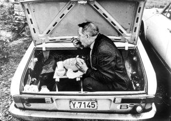 Mann isst im Kofferraum