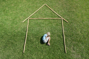 Boy in fetal position within outline of house  high angle view