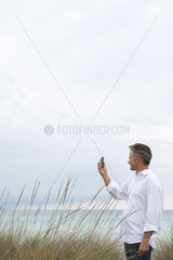 Mature man photographing scenery with cell phone
