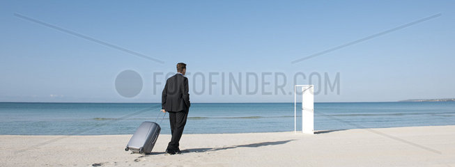 Businessman pulling suitcase on beach  walking towards half-open door