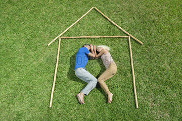 Couple lying on grass within outline of house  high angle view