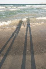 Shadows of couple on beach