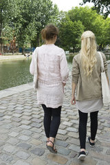 Young women walking together  rear view