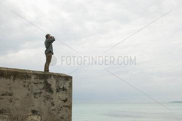 Mature man looking at view through binoculars