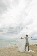 Man trapped in plastic on beach