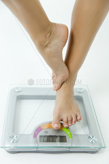 Woman standing on one leg on bathroom scale  low section